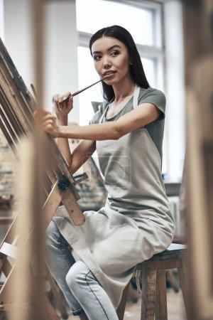 Photo pour Jeune belle femme peintre tout en travaillant dans un studio, souriant à la caméra - image libre de droit