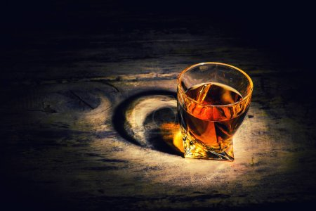 Photo for Whiskey with ice cubes on wooden background - Royalty Free Image
