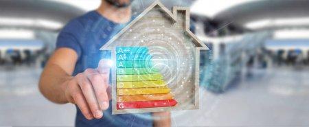 Photo pour Homme d'affaires sur fond flou en utilisant le tableau d'évaluation de l'énergie de rendu 3D dans une maison en bois - image libre de droit