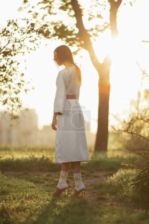 Photo pour Femme asiatique portant kimono japonais traditionnel à la mode en plein air dans le parc. Élégant modèle japonais gracieux posant à l'extérieur en robe à la mode au coucher du soleil. Jeune fille souriante marchant par le sentier dans son intégralité - image libre de droit