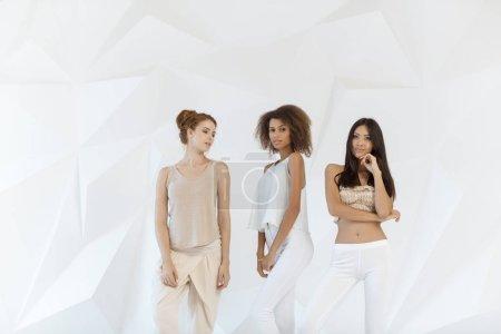 Photo pour Groupe d'amis de races différentes. Diverses femmes debout ensemble sur fond blanc polygone à l'intérieur. Multi ethniques femelles en regardant la caméra en studio. - image libre de droit