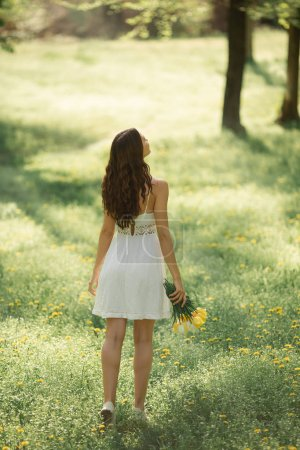 Photo for Rear view og attractive woman in white dress with a bouquet of spring flowers walking against nature bokeh green background. Creative photo of gorgeous young mixed race Caucasian Asian brunette girl - Royalty Free Image
