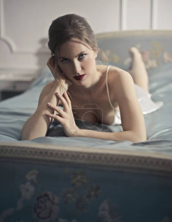 Young blonde woman lying on her bed and looking seductively.