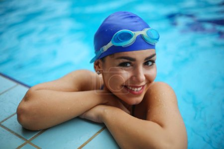 Photo for Beautiful young woman smiling at the edge of a swimming pool wearing swimming cap and goggles. - Royalty Free Image