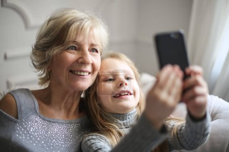 Smiling grandmother and granddaughter taking a selfie together.