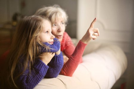 Grandmother showing something amazing to her granddaughter.