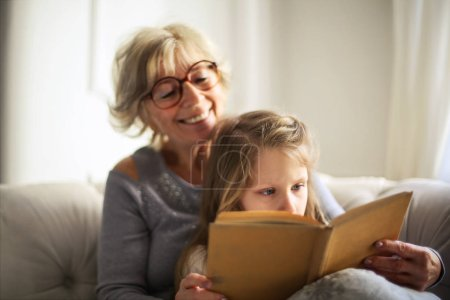 Grandmother and granddaughter reading together a book.