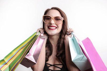 Photo pour Femme heureuse avec des sacs à provisions colorés et des lunettes de soleil . - image libre de droit