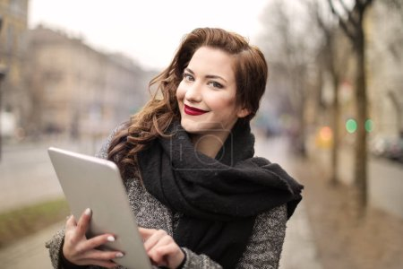 Young beautiful woman using her tablet on the street in the city.