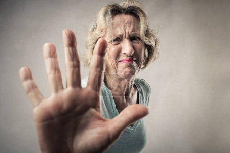 Senior woman showing her palm as refusing or denying.
