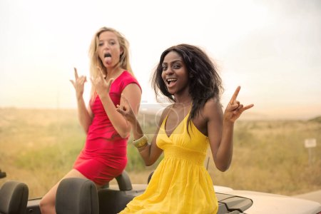Beautiful young blonde woman showing tongue with a black beautiful woman cheering happily on the backseat of a cabrio in summer.