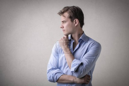 Young businessman thinking in a rolled up shirt.