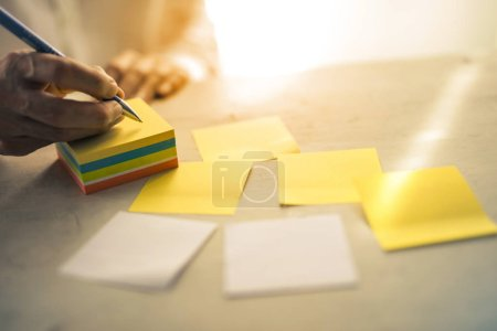 A hand writing notes on sticky note.