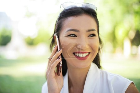 Asian elegant woman talking on her smartphone and smiling outdoor on a sunny day.