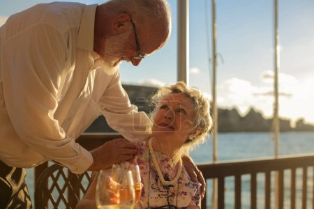 Senior couple relaxing on a terrace on a sunny day with the sea in the background.