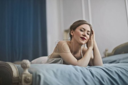 Photo for Beautiful blonde woman lying on a bed and relaxing. - Royalty Free Image