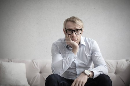 Blond man with glasses thinking desperately on a c...