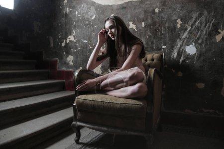 Photo pour Triste jeune femme assise dans un fauteuil et pensant désespérément. - image libre de droit