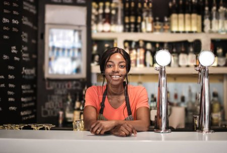 Black young woman smiles in front of a bar in a bistro.