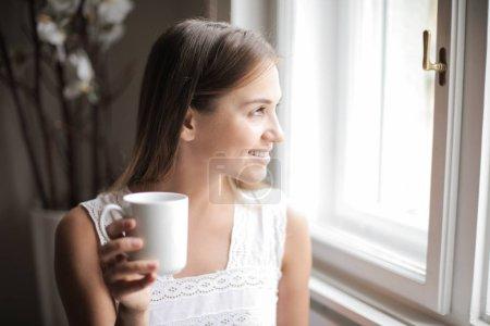 Photo pour Jeune femme dégustant une tasse de boisson à la maison . - image libre de droit