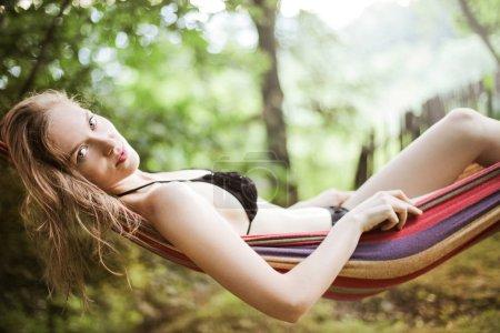 Blonde woman relaxing in a hammock.