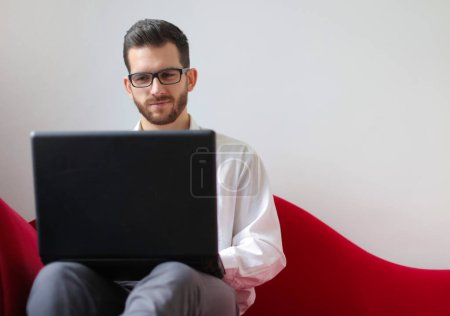 Photo for Man sitting on a sofa with a laptop. - Royalty Free Image
