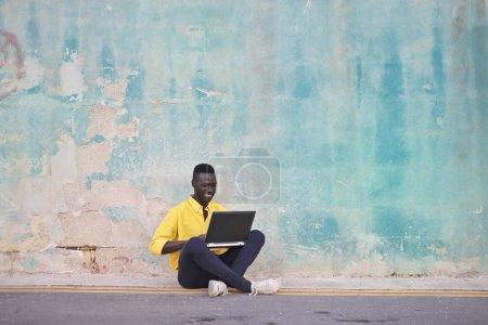 Photo pour Jeune bel homme regardant et tenant un ordinateur portable tout en étant assis à côté du mur - image libre de droit