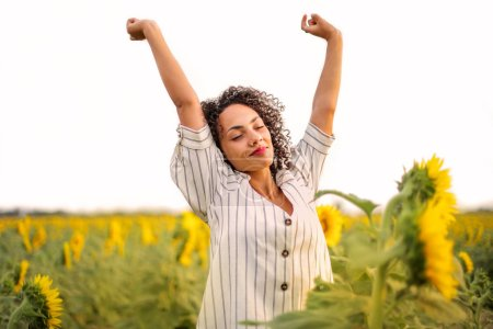 Photo for Beautiful black woman enjoying freedom  in the sunflower field - Royalty Free Image