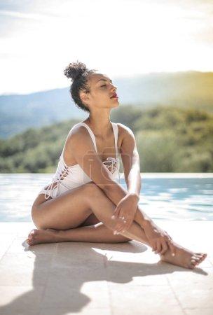 Photo pour Belle jeune femme relaxante au bord de la piscine - image libre de droit