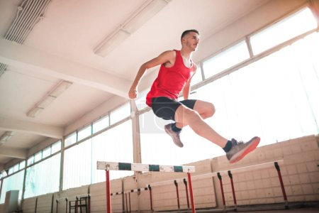 Photo for Man athlete jumping over an obstacle - Royalty Free Image
