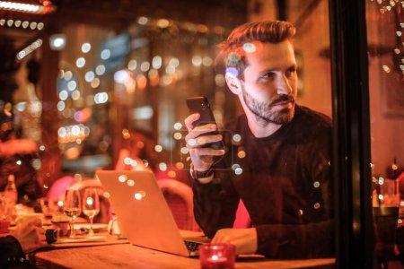 Photo pour Bel homme avec ordinateur portable et smartphone portrait - image libre de droit