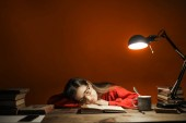 Young woman sleeping over her book at the desk