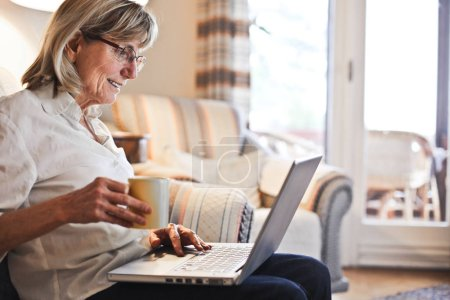 Photo for A woman with laptop sitting on the sofa while she drinking a coffee - Royalty Free Image