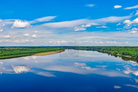 Photo for Clouds in the sky reflected in a calm Vishera river on a summer day. - Royalty Free Image
