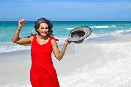 Photo for Beautiful Mature Woman Wearing a Red Summer Dress on the Beach - Royalty Free Image