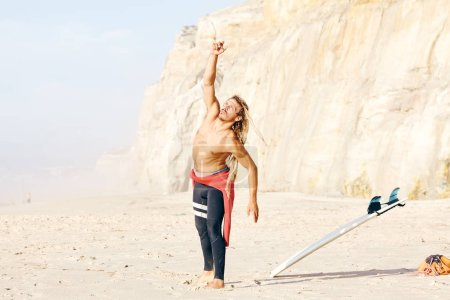 Photo for Young adult shirtless surfer with dreadlocks wearing wetsuit warming up on beach preparing for summer evening surfing session - stretching routine for surfing and active lifestyle concept, Portugal - Royalty Free Image