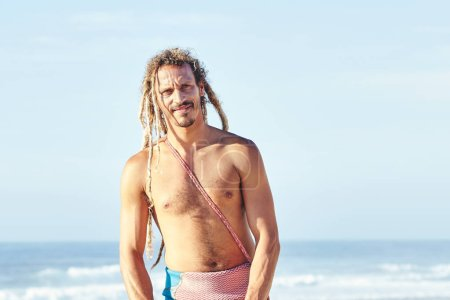 Photo for Portrait of young adult shirtless surfer with dreadlocks standing and smiling on beach against surfing spot before summer evening session - surfing and extreme sport concept. Baleal, Peniche, Portugal - Royalty Free Image