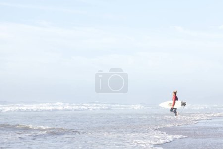 Young adult surfer with dreadlocks wearing wetsuit entering foggy ocean with surfboard under arm to catch waves during summer evening surf session - active lifestyle and surfing concept, copy space