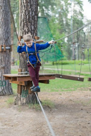 Photo for A little boy is training in a rope park. The child climbs the obstacle course. Active recreation in the park in the fresh air. - Royalty Free Image