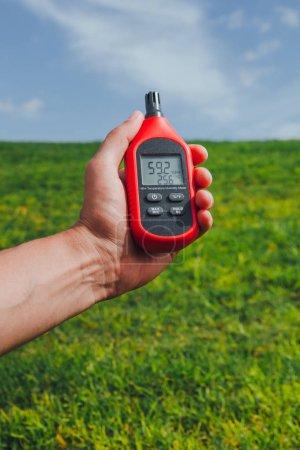 Photo pour Thermomètre portable dans la main de mesure humidité et température d'air extérieur - image libre de droit