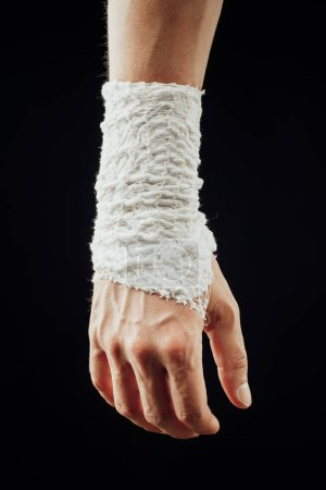 Photo for Wrist wrapped with healing bandage, isolated on black - Royalty Free Image