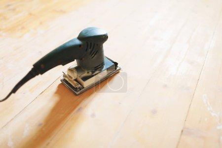 Photo pour Ponçage du sol en bois avec outil ponceuse plat - image libre de droit