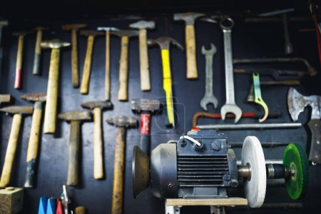 Photo for Grinding machine in old garage, wall with rusty hammers background - Royalty Free Image