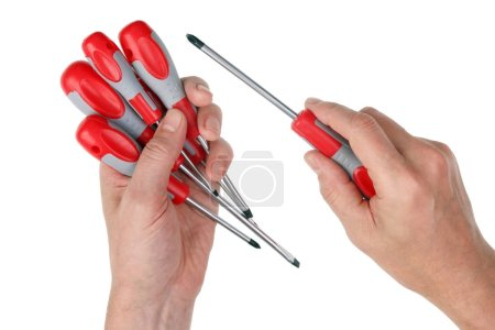 Elderly male home craftsman selects the necessary  mass production screwdriver from the set. Isolated on white studio closeup shot