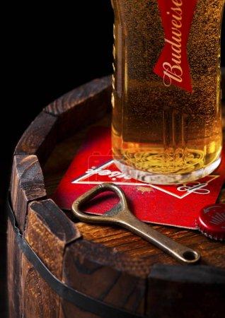 Photo pour Londres, Uk - 27 avril 2018: Original verre de bière budweiser avec ouvreur coater et bouteille de bière sur en bois Canon, une lager américaine apparue en 1876.. - image libre de droit