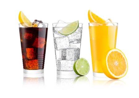 Verres de cola et soda orange boisson et limonade eau gazeuse sur fond blanc avec glaçons citrons et morceaux de citron vert