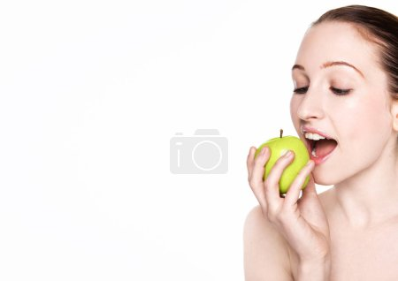 Photo for Beautiful fitness woman eating healthy apple on white background - Royalty Free Image