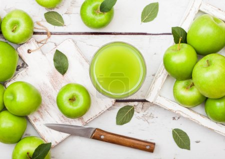 Photo pour Glass of fresh organic apple juice with granny smith green apples in box on wood background. - image libre de droit