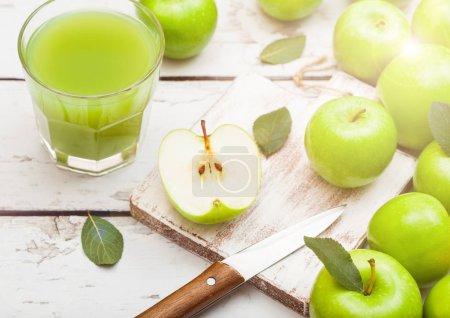 Photo for Glass of fresh organic apple juice with granny smith and british bramley apples on wooden background. - Royalty Free Image