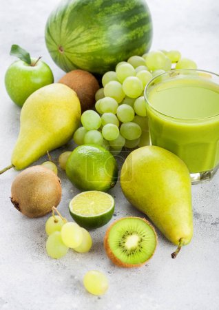 Photo pour Glass of fresh smoothie with organic green toned fruits on stone kitchen table background. Pear and grapes with kiwi and lime with apple. - image libre de droit